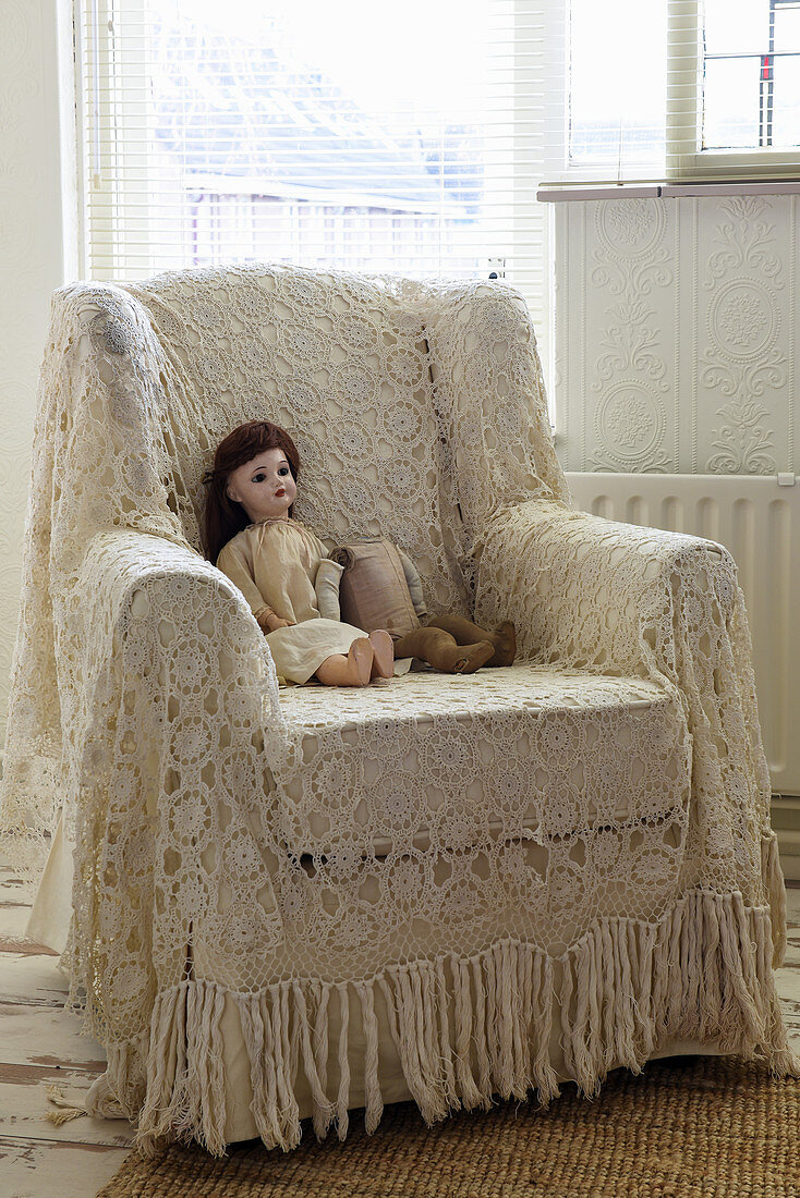 Doll on armchair with crocheted throw