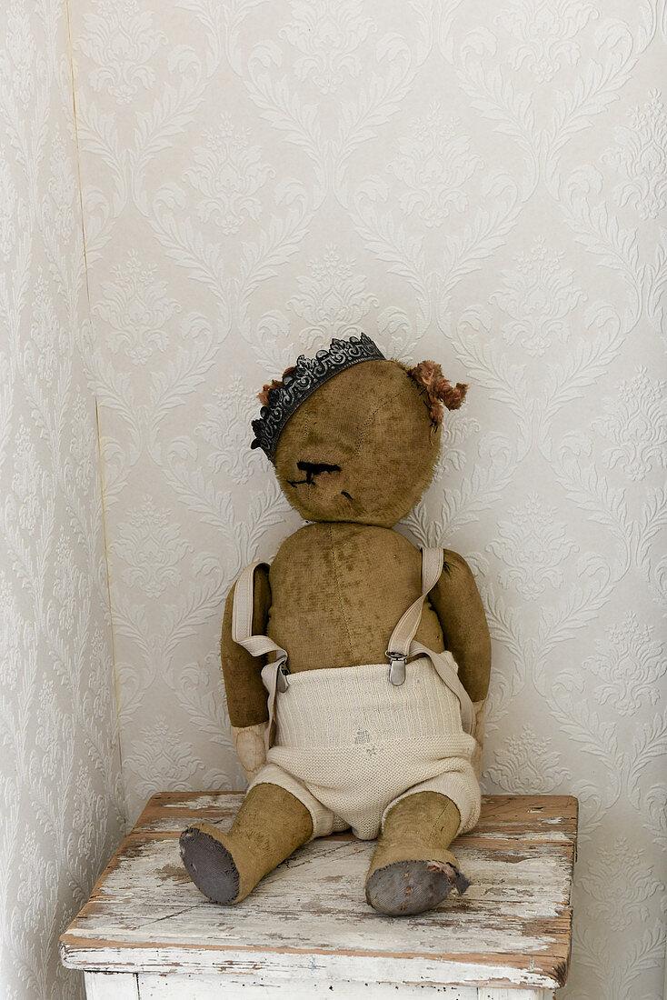 Vintage-style arrangement of old, threadbare teddy bear wearing a crown