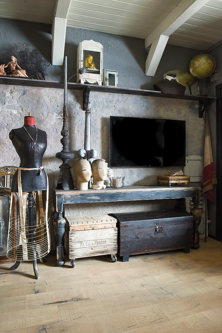 Tailors' dummy next to old console table, trunks and TV