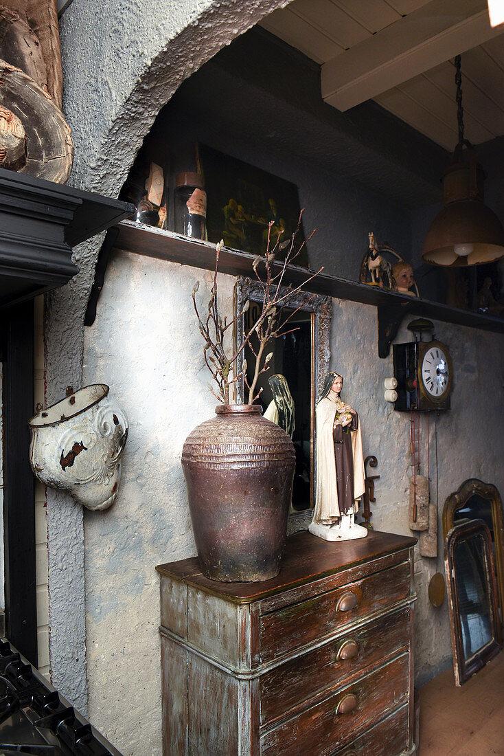 Steingutvase mit Zweigen und Madonnenfigur auf einer Kommode