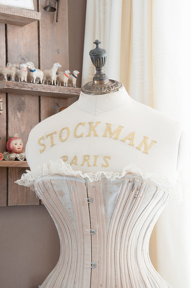 Vintage-style arrangement of embroidered tailors' dummy wearing corset