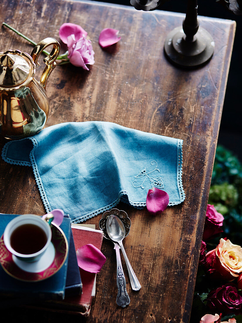 Coffee dishes and silver spoons on vintage wooden table
