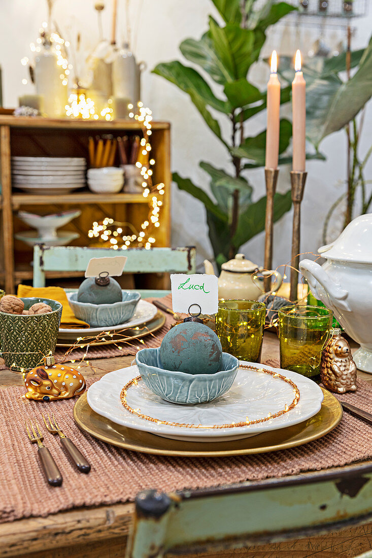 Dining table festively decorated with balls, candles and fairy lights