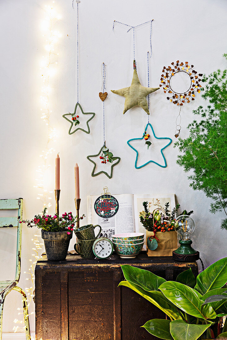 Antique trunk used as table below various handmade star decorations on wall