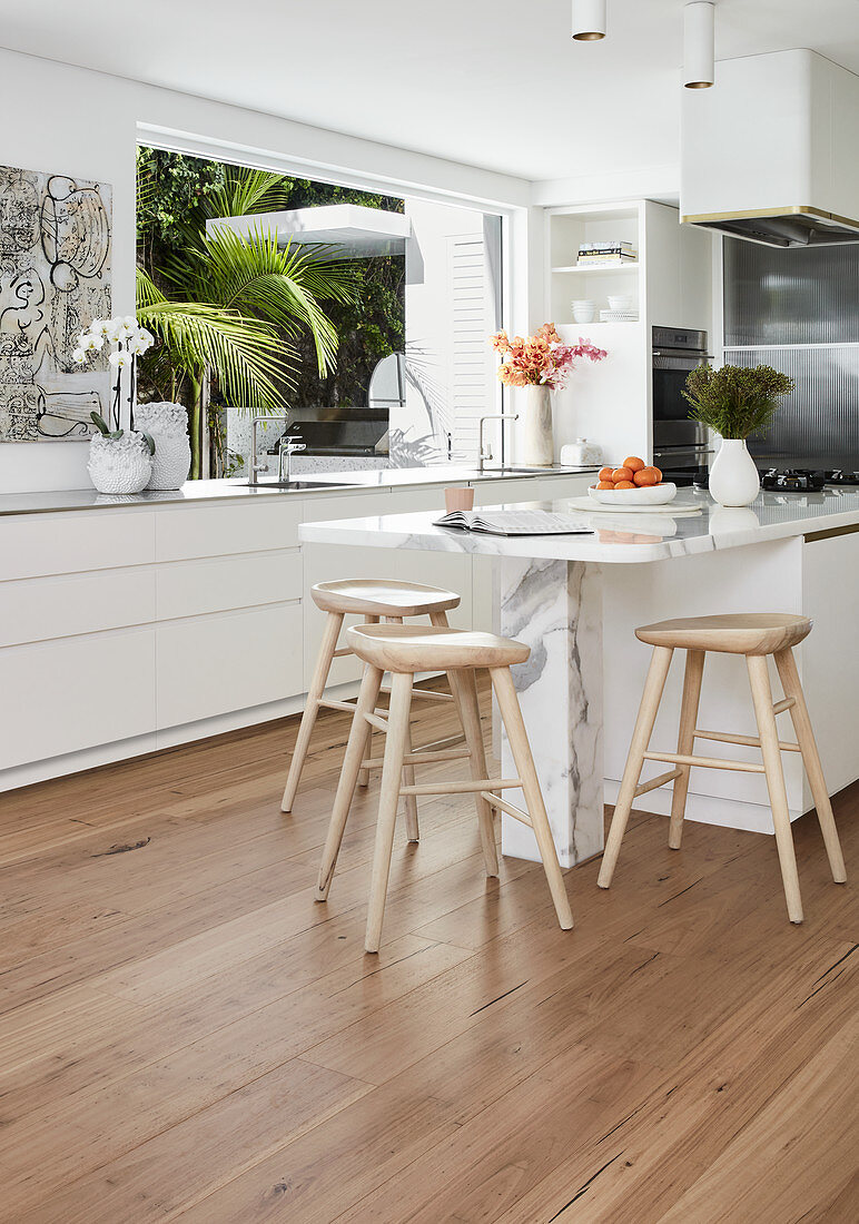 Bar stools at marble counter in white, modern kitchen