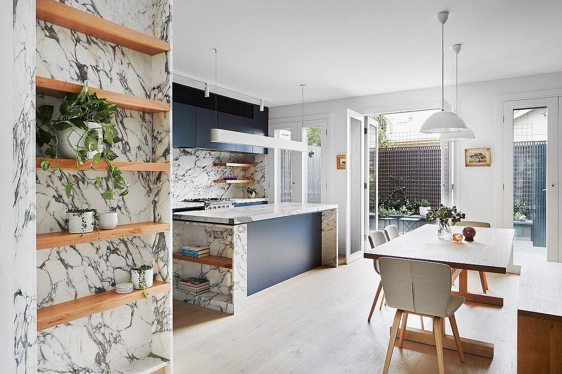 Moderner Wohnraum mit Küche, Esstisch und Marmorverkleidung