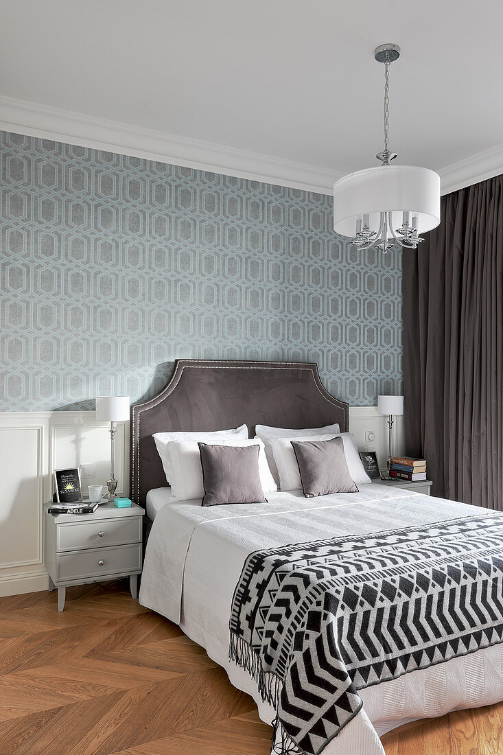 Patterned wallpaper and panelled wainscoting in elegant bedroom