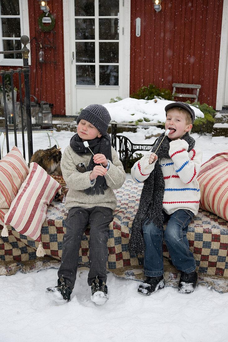 Kinder mit Marshmallow-Spießen auf verschneiter Terrasse
