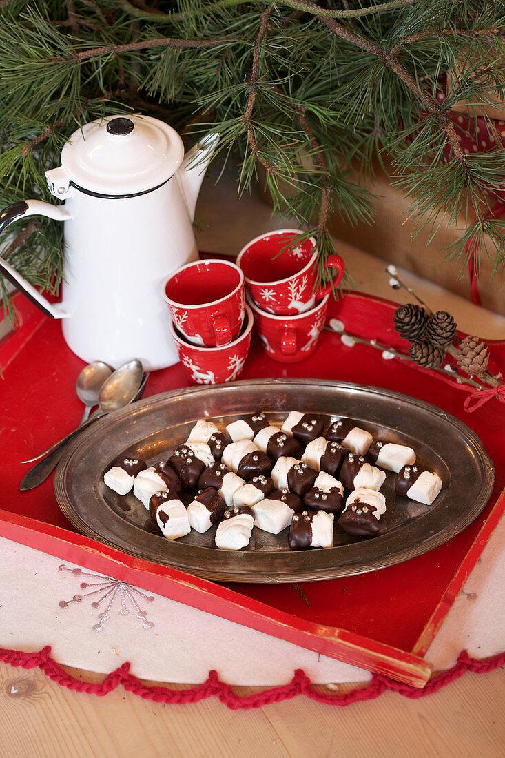 Marshmallows mit Schokoglasur, Tassen und Kanne auf rotem Tablett
