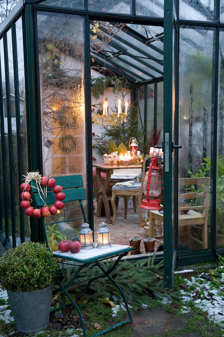 Wreath of apples on chair outside festively decorated conservatory