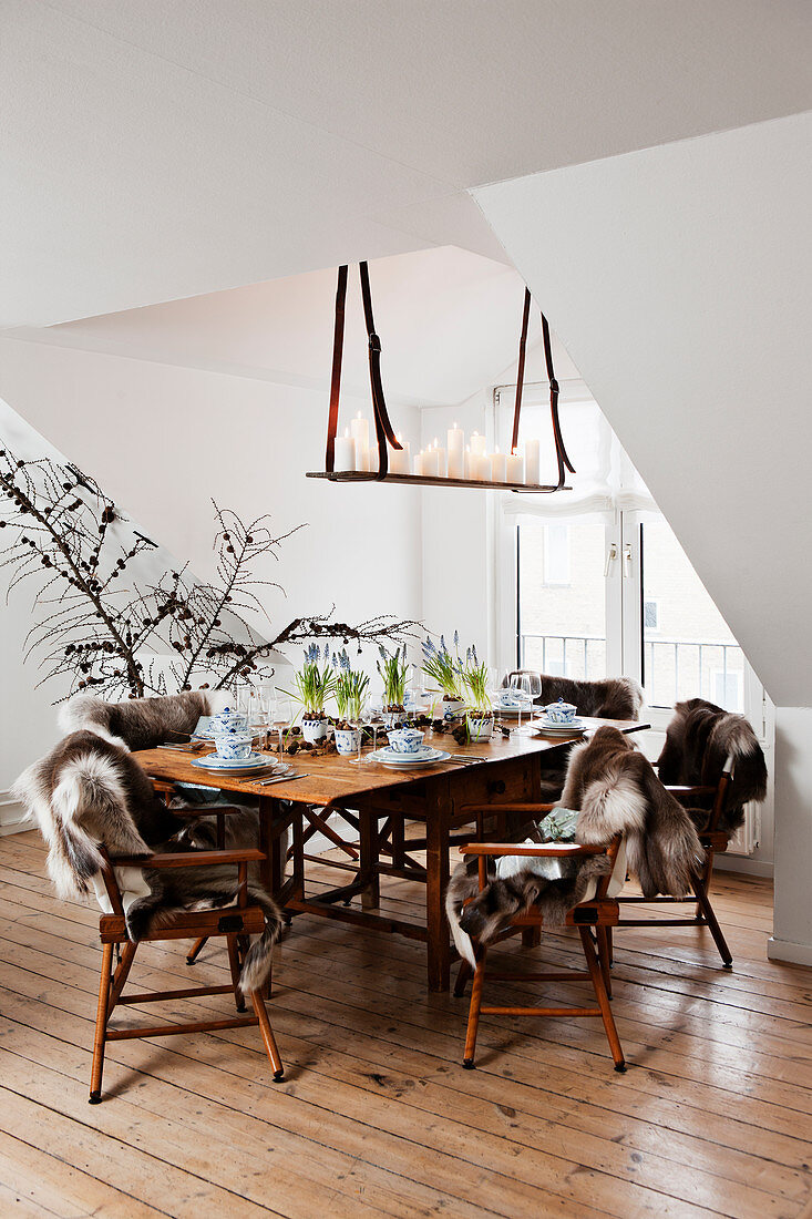 Set table and chairs with fur blankets below DIY candle chandelier