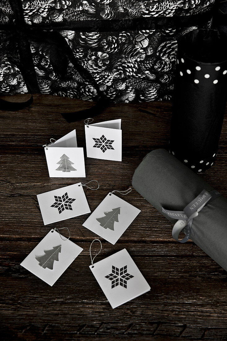 Gift tags with Christmassy motifs on wooden table