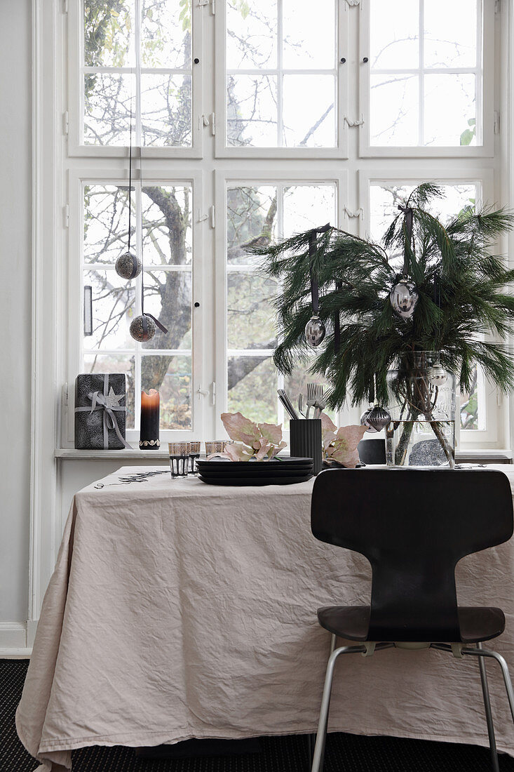 Black chair at festively decorated table with pale tablecloth