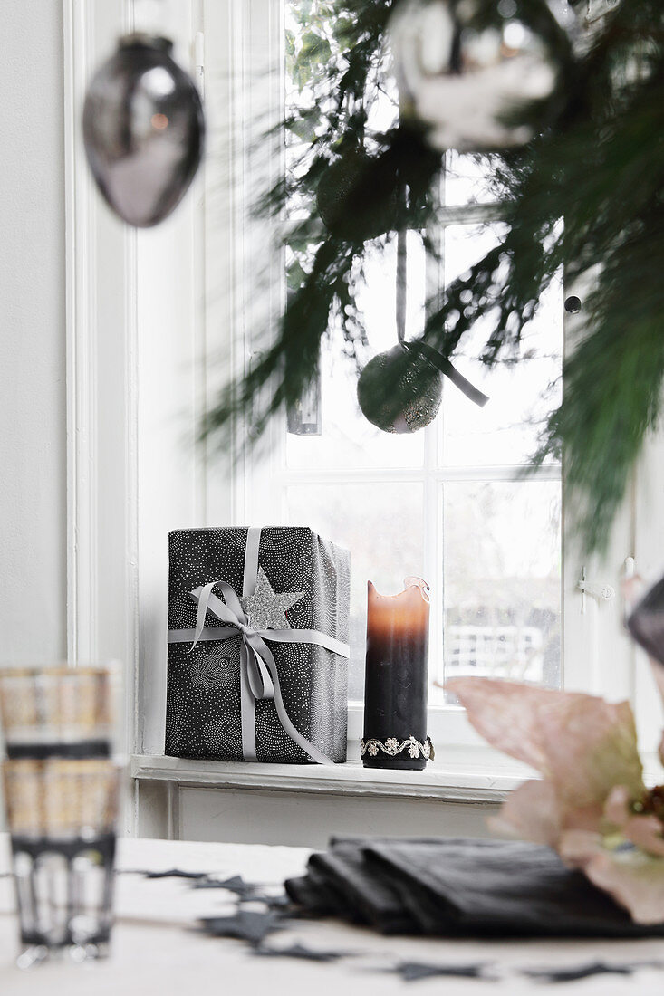 Gifts and candle on windowsill
