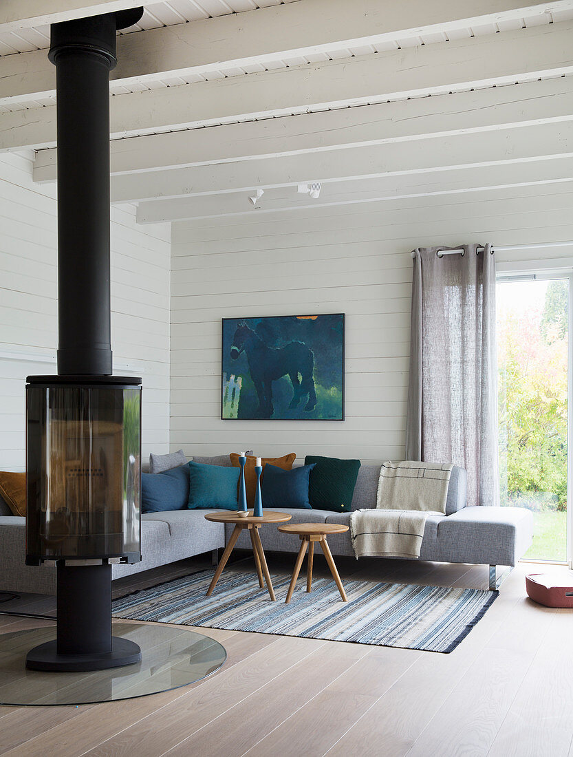 Fireplace and corner sofa in living room with white-painted wood cladding