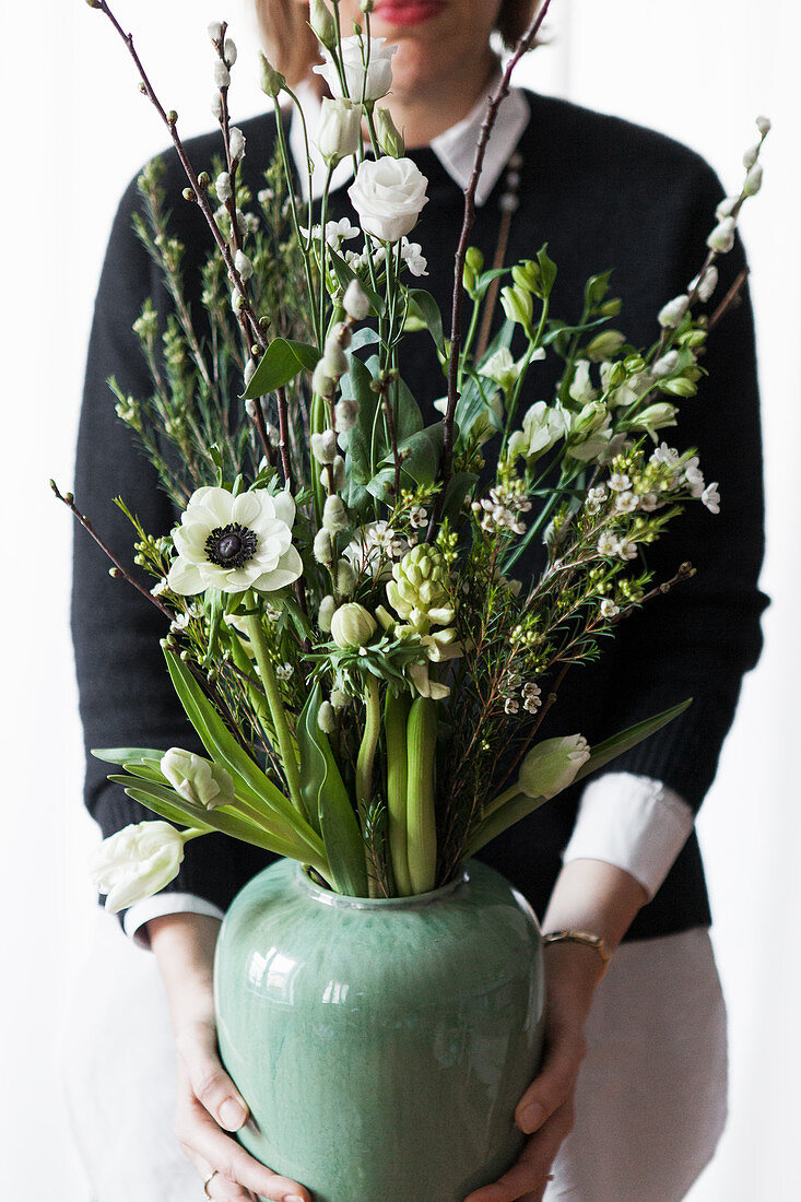 Vase of white spring flowers: tulip, anemone, willow catkins, waxflower, hyacinths, star-of-Bethlehem, lisianthus and cherry branch