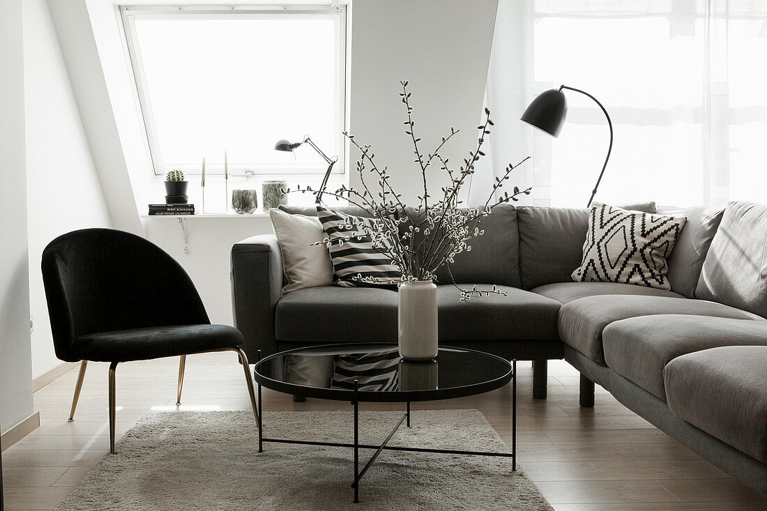 Grey sofa, black chair and coffee table with vase of branches