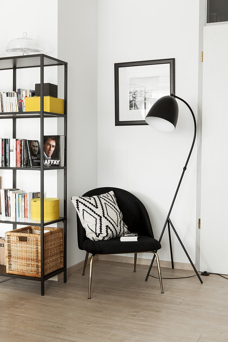 Black chair with scatter cushion between standard lamp and shelves in corner