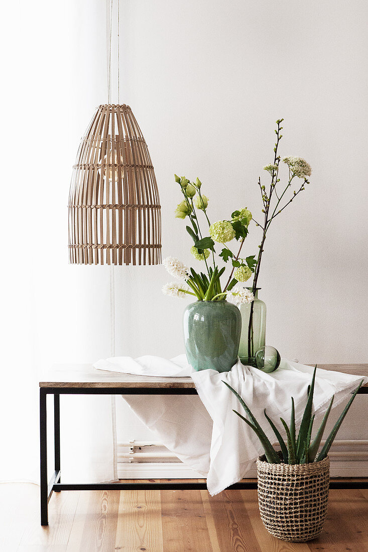 Branches of viburnum and hyacinths on coffee table below pendant lamps