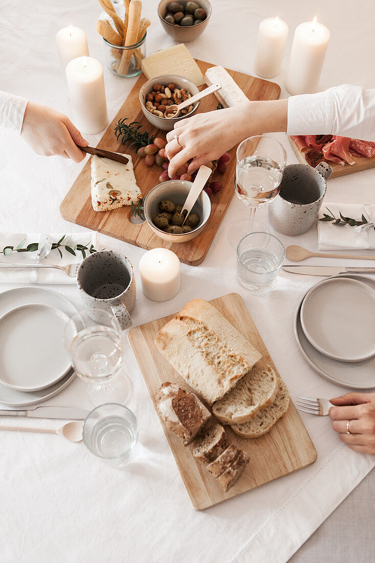 Cheeseboard and bread on table set with white tablecloth and candles