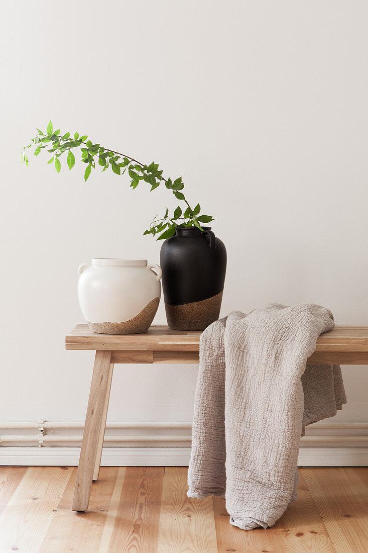 Ceramic vases and linen blanket on wooden bench