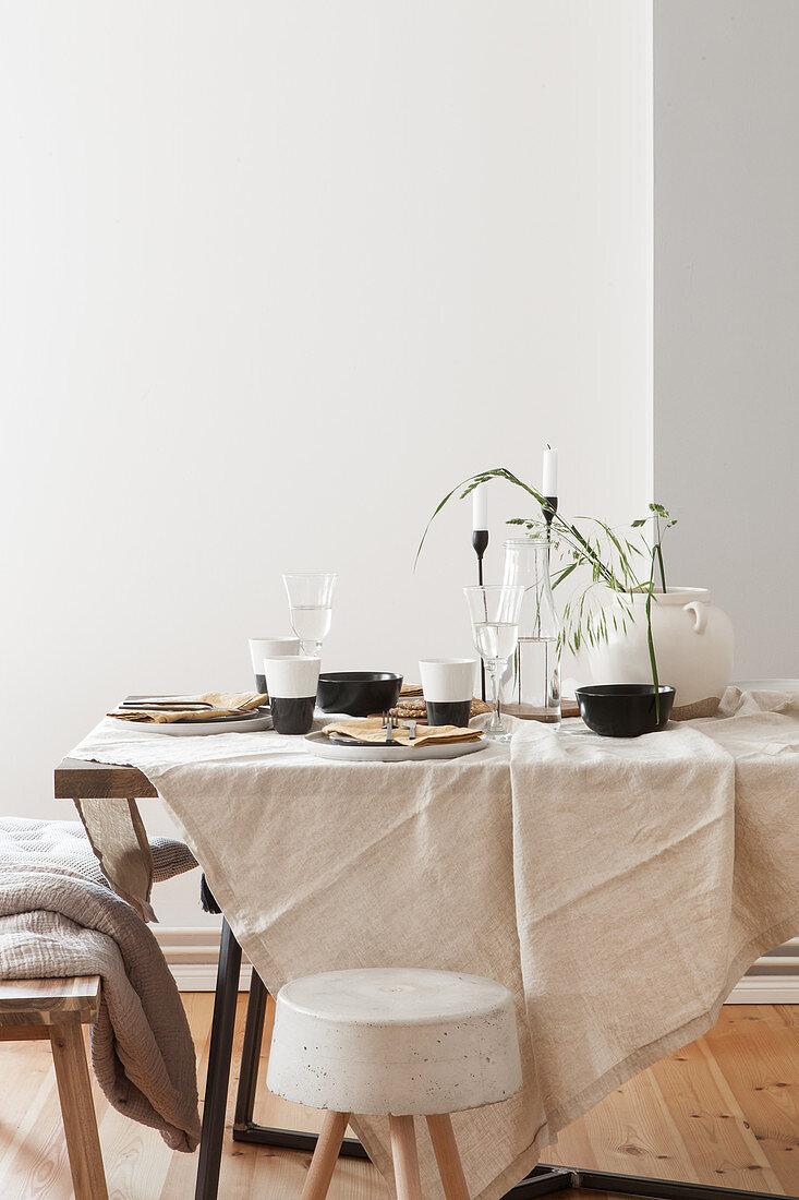 Gedeckter Tisch mit naturfarbener Tischdecke und schwarz-weißem Geschirr