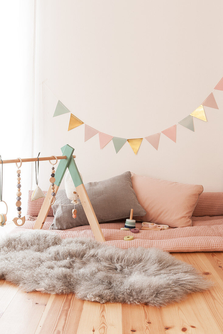 Indoor play area with baby's activity centre on fluffy fur rug and bunting
