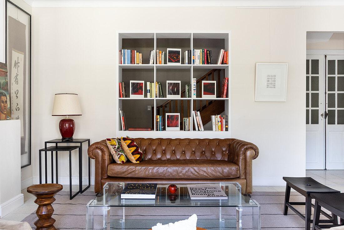 Braune Ledercouch und Acryltisch vor Regal im Wohnzimmer