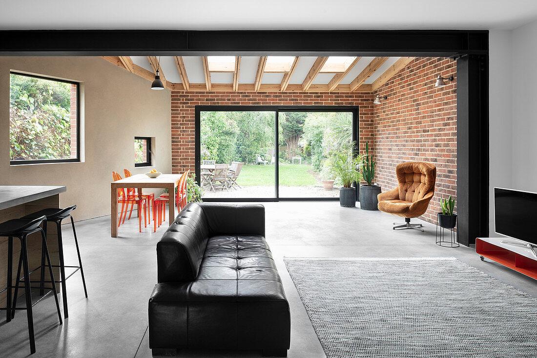 Offener Wohnraum mit schwarzer Ledercouch, im Hintergrund Backsteinwand
