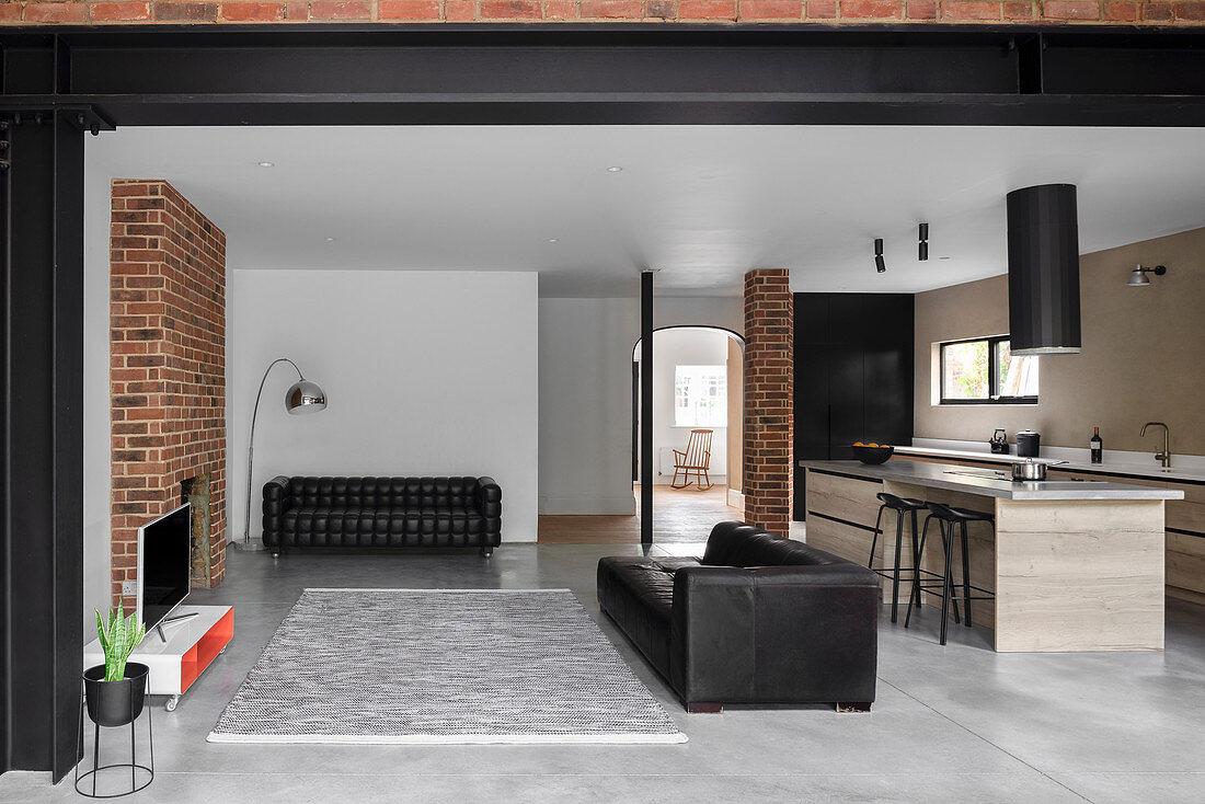 Offener Wohnraum mit schwarzer Ledercouch und teilweise Backsteinwand