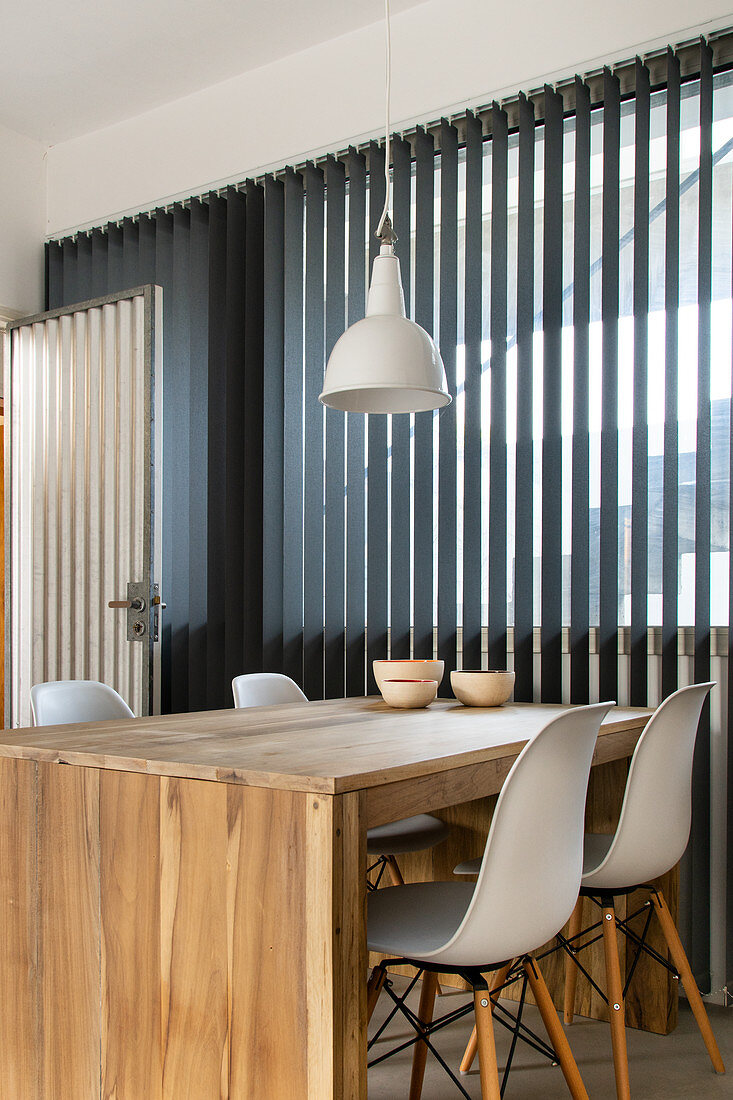 Esstisch aus Holz mit Klassikerstühlen am Fenster
