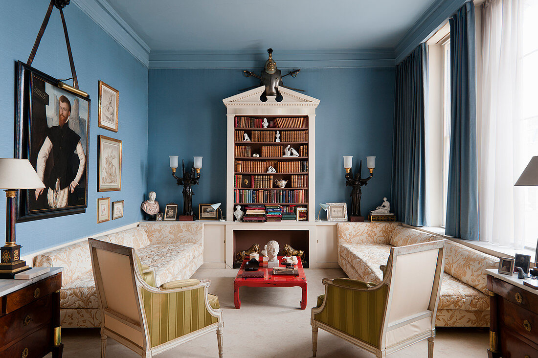 Symmetrical, Wedgewood-blue sitting room with bookcase, sofas, red lacquered coffee table and historical portrait