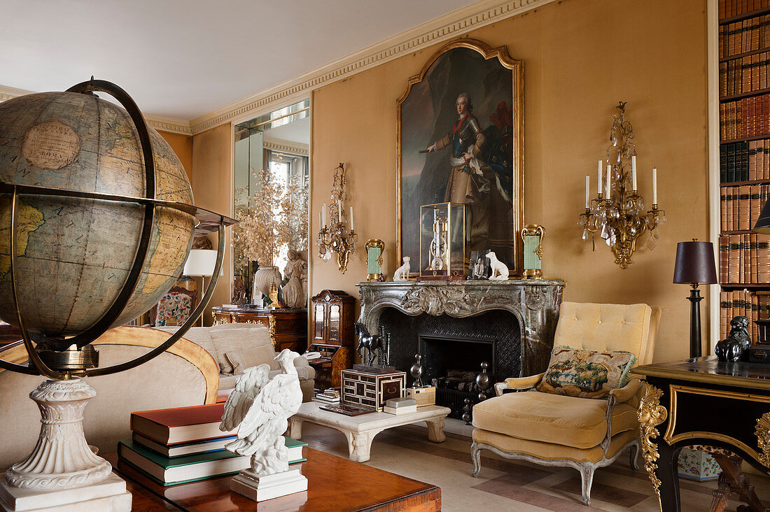 Large Georgian portrait above marble fireplace in drawing room with wall sconces and old globe