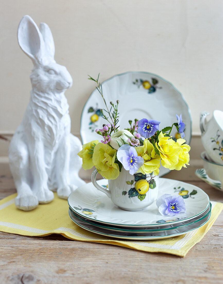 Posy of primulas, violas, lisianthus and waxflowers on Easter table