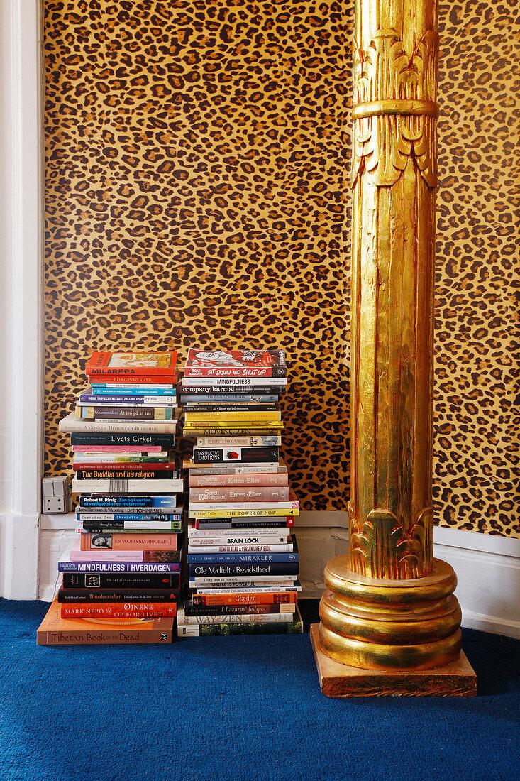 Stacked books, golden pillar and leopard-print wallpaper