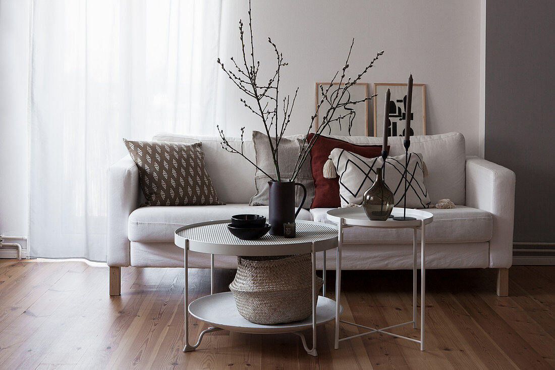 Pale sofa with scatter cushions and round coffee table decorated with branches
