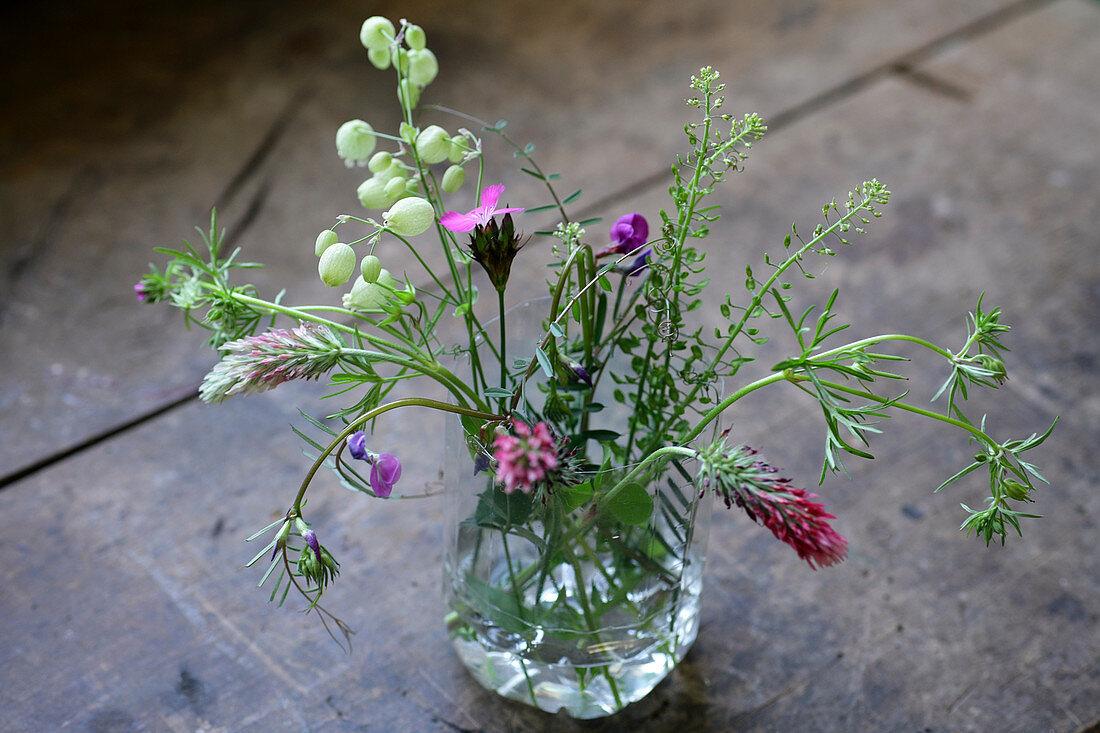 Wild flowers bouquet in glass of water