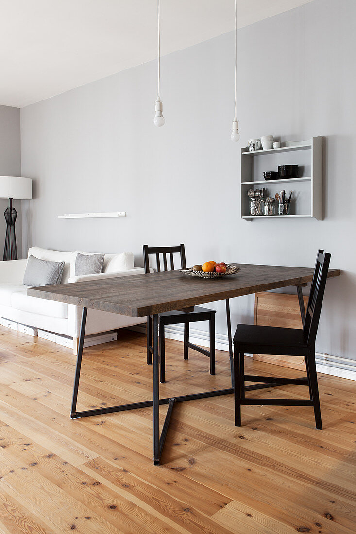 Dining table with dark wooden top and black chairs in open-plan interior