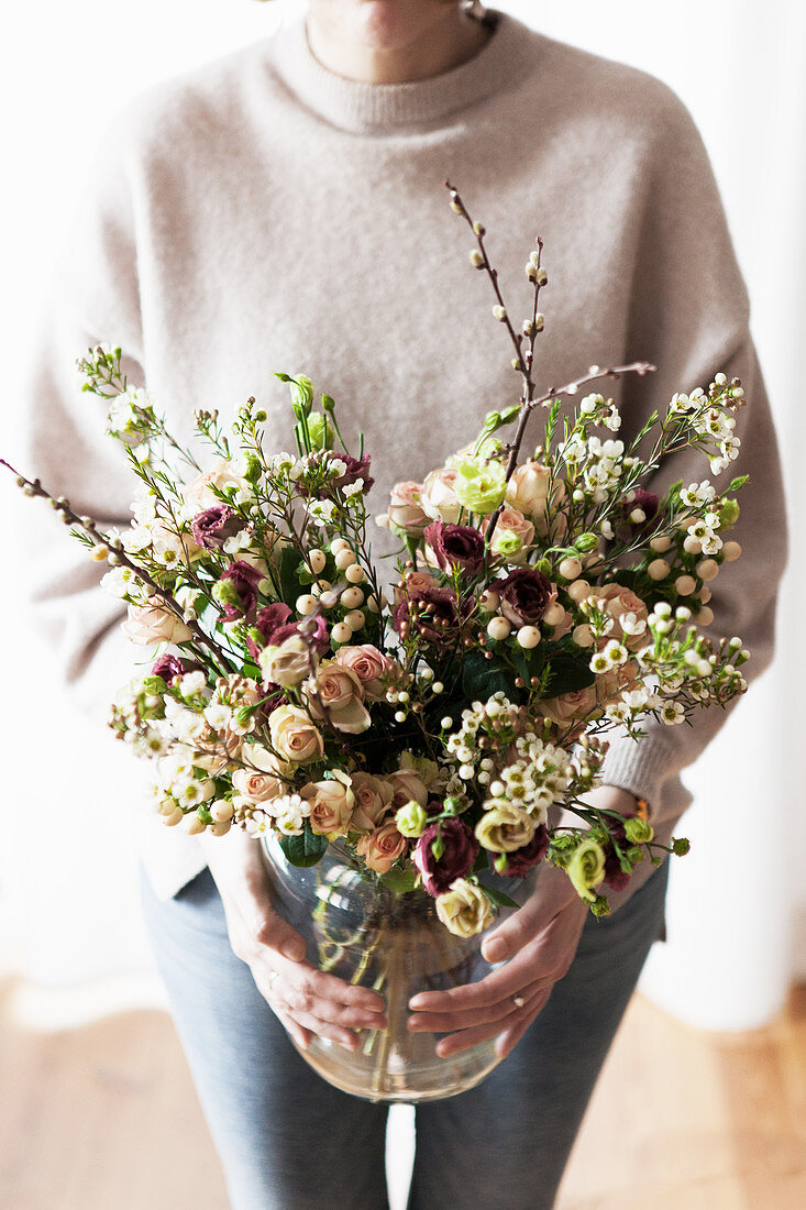 Woman holding vase of roses, waxflowers, St. John's wort with white berries and willow catkins