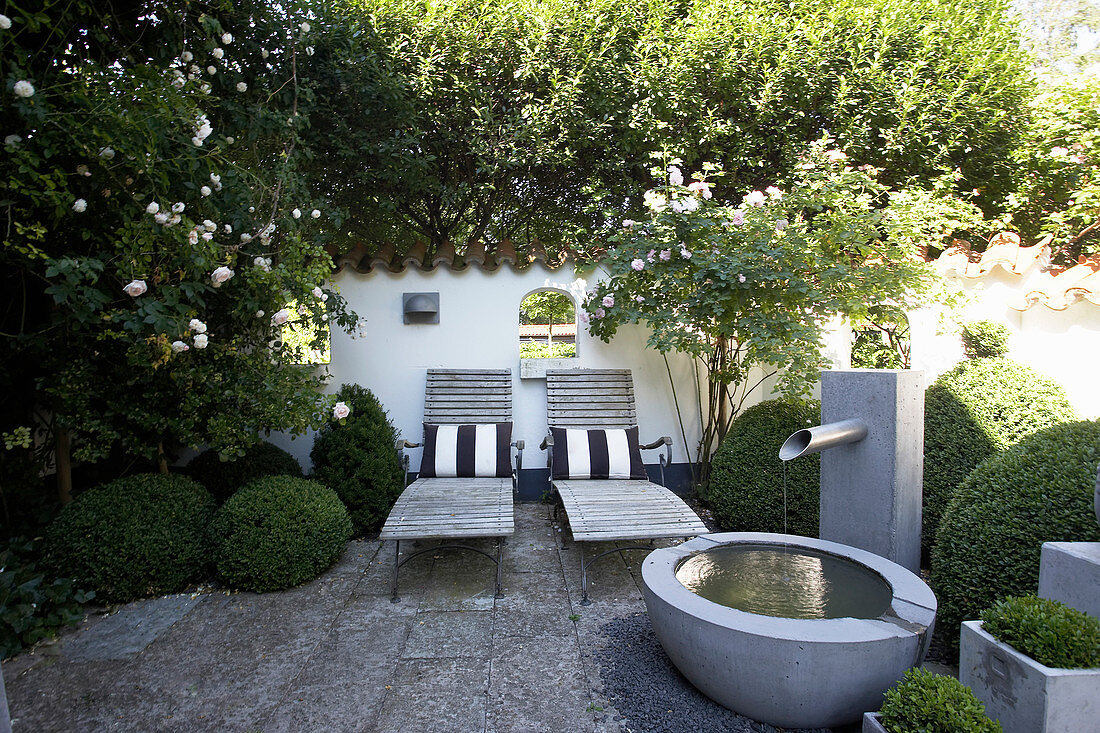 Zen garden in summer with water feature and loungers
