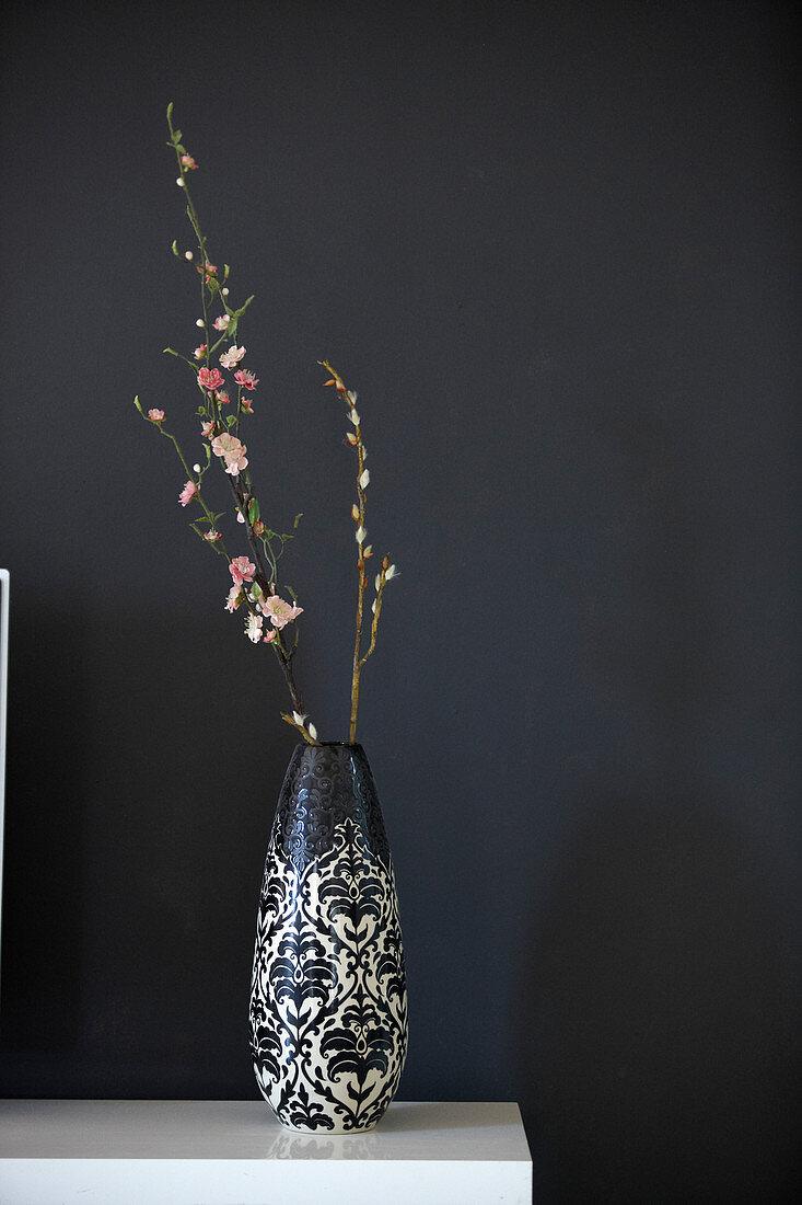 Flowering branch in vase against black wall
