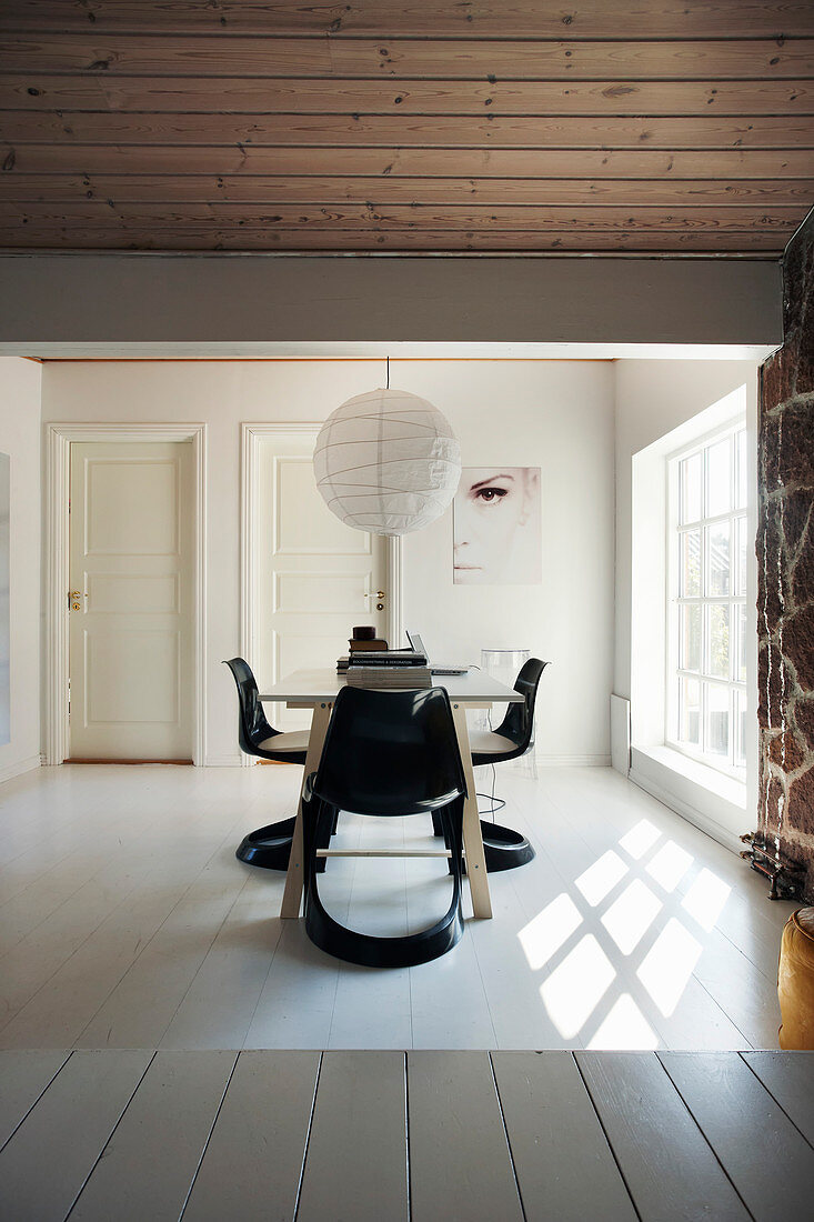 Dining table with designer chair next to lattice window