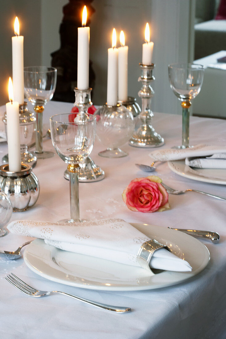 Table set in white with candles and pink roses