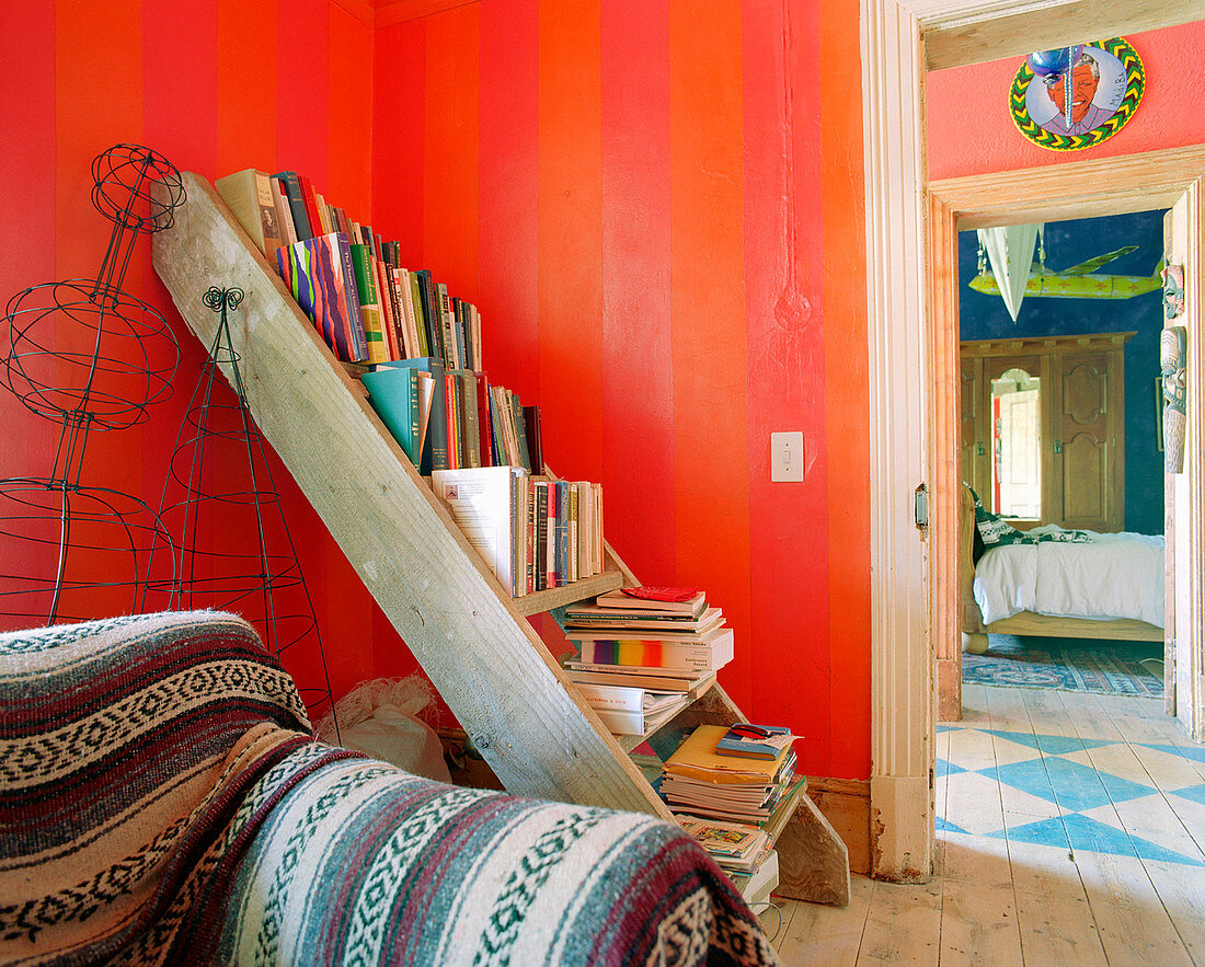 Old ladder used as bookshelves in room with red walls