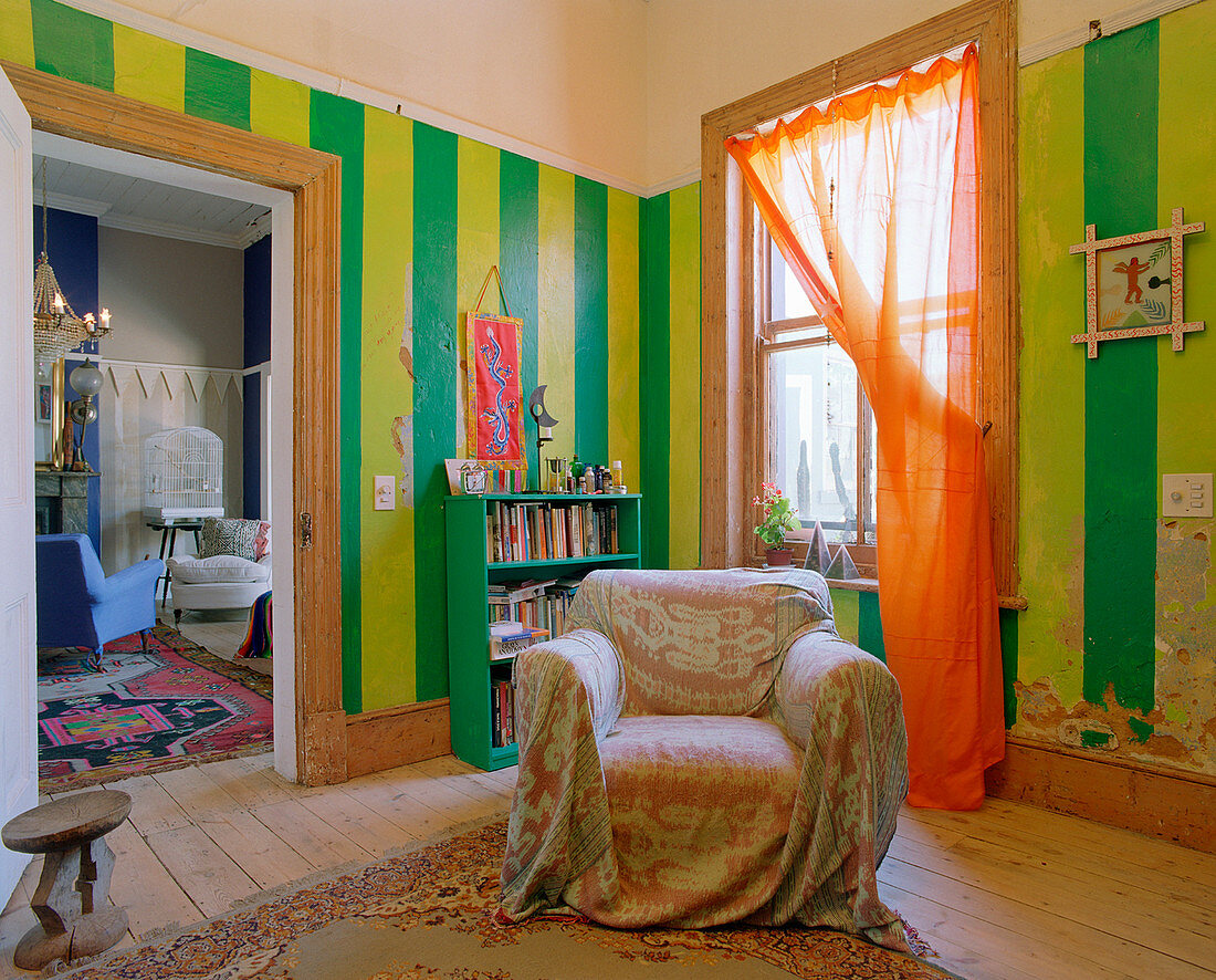 Armchair in front of bookcase in room with green and yellow striped walls