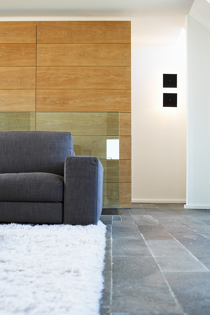 Grey sofa on white rug against oak wall-cladding in living room