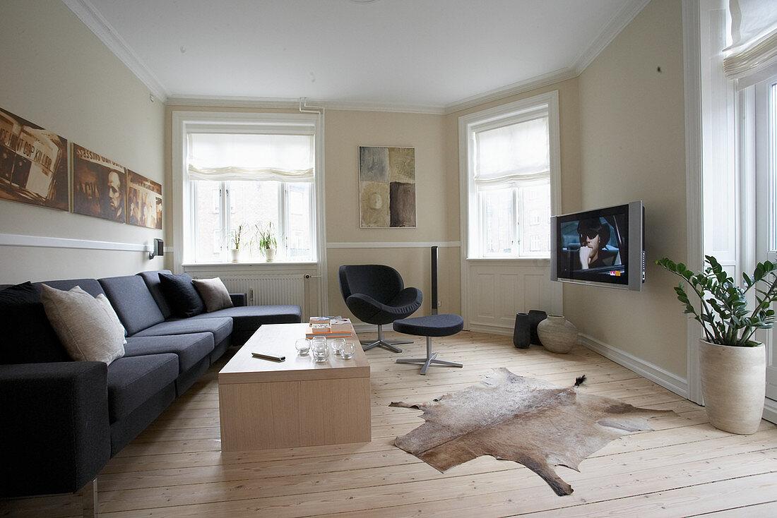 Dark grey sofa, armchair, TV, coffee table and animal-skin rug in living room
