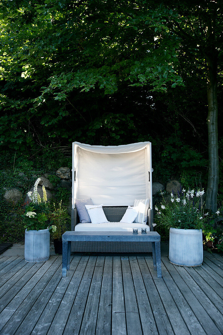 Lounge sofa with canopy and planters on wooden deck