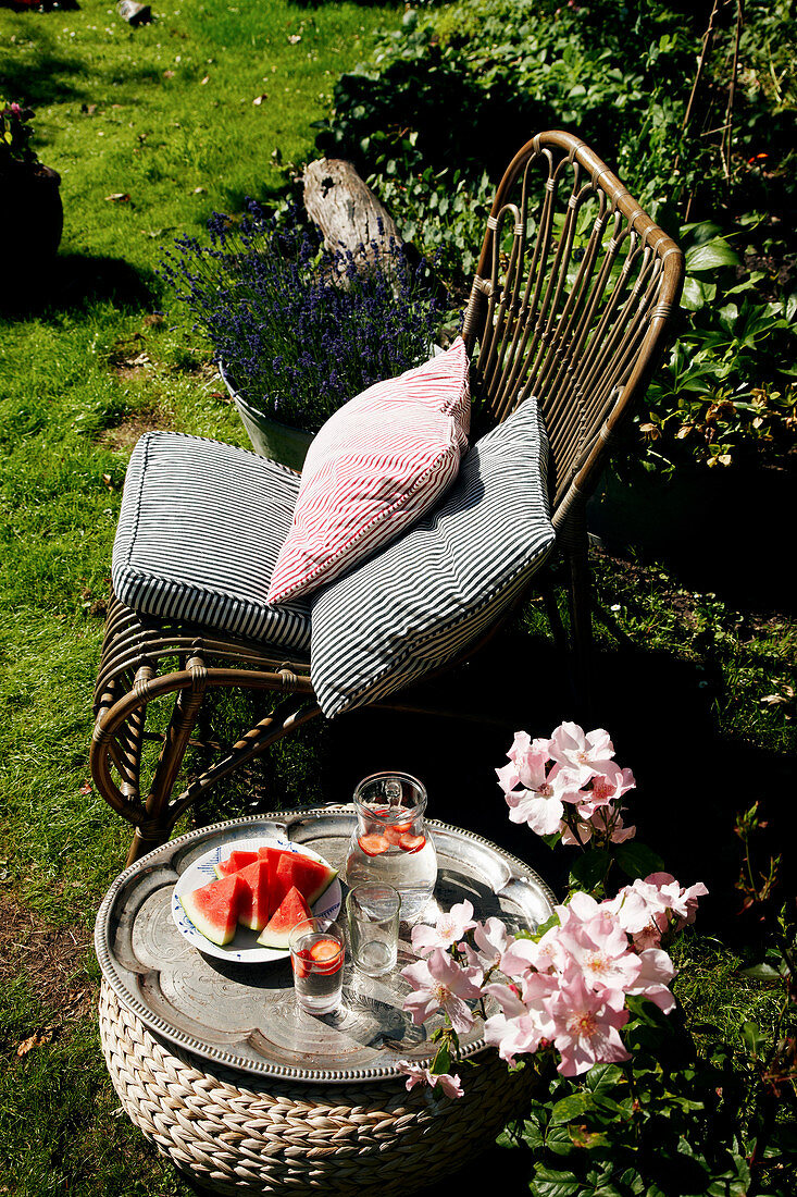 Rattan chair with cushions next to tray of melon in garden
