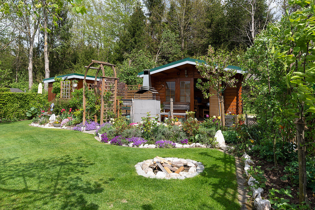 British garden with garden and tool shed, perennial bed, lawn, and fireplace
